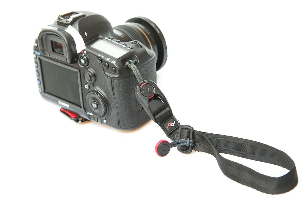 Zápěstní popruh připevněný k fotoaparátu.