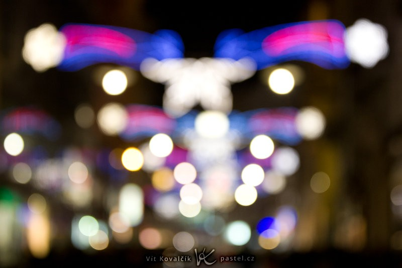 Rozmazaná ulice ozdobená vánočními světly. Bez nich by už v tuto dobu (čtvrt na šest) panovala hluboká tma. Canon EOS 5D Mark II, EF Canon EF 70–200 mm F2,8L II IS USM, 1/80 s, F2,8, ISO 1600, ohnisko 75 mm.