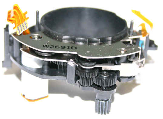 Micro motor z objektivu Canon EF 75-300. Nahoře je tubus s čočkou, kterou motor pohybuje. Celý mechanismus je tedy obestavěný kolem ní do tvaru oblouku. Foto electricstuff.co.uk