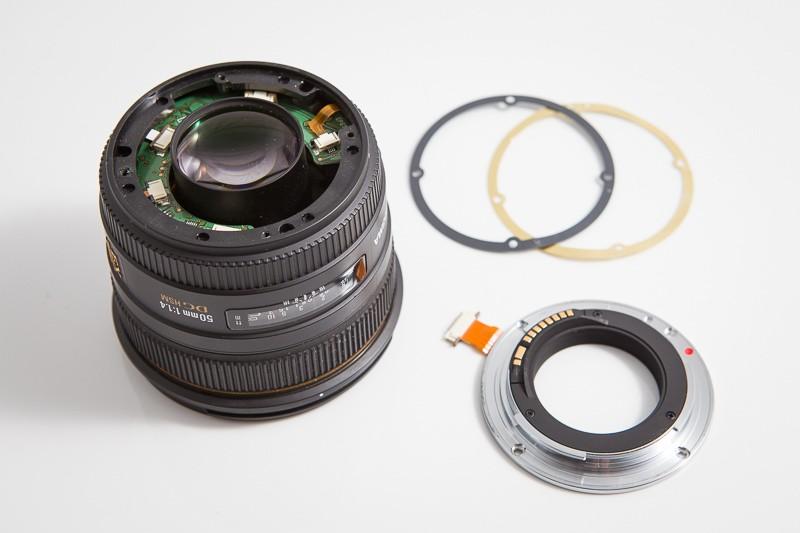 Sigma 50 mm F1,4 EX DG HSM s ulomenou objímkou. V pozadí můžete vidět kroužky, které se do objektivu vkládají pro přesné seřízení vzdálenosti čoček od senzoru – hraje se zde o zlomky milimetru.
