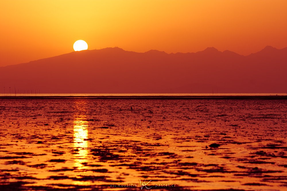 Slunce protínající siluetu hor. Canon 40D, Canon EF-S 55-250/4-5,6 IS, 1/80 s, f/10, ISO 200, ohnisko 123 mm